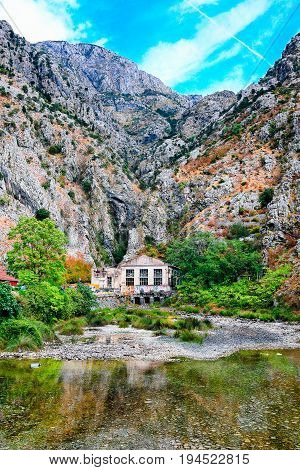 Mediterranean landscape. Overhanging cliffs, old power station and river.