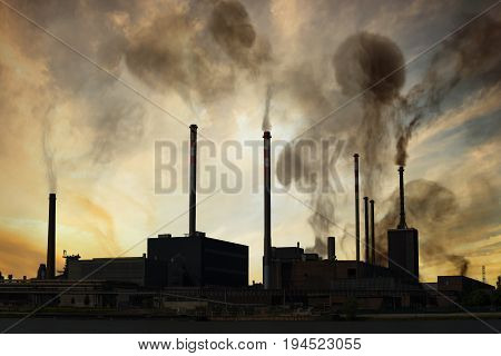 Air pollution and smog concept. Factory is producing toxic smoke at sunset.