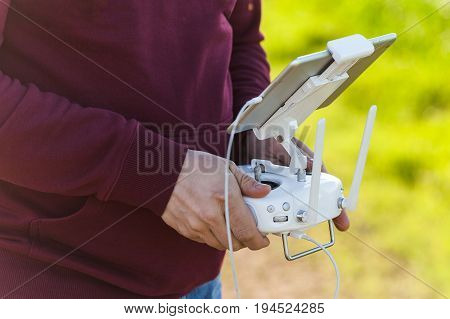 quadcopter flight outdoors, aerial imagery and tech hobby, recreation concept - closeup on men hands of drone operator with a beautiful white remote control, visual observation of flight and shooting