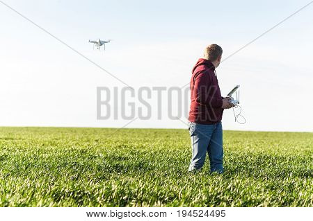 quadcopter summer outdoors, aerial imagery and hobby concept - copter flies up to male operator from back, pilot control white drone speed of flight, at background of sky and field of green grass