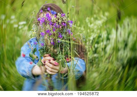 Young girl with long hair offering wildflowers for us, focus on it. Close-up of bright bouquet of wildflowers in girls hands. Selective focus. Concept of seasons, environmental and ecology, green planet, natural background.
