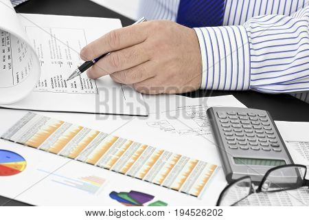 Businessman with pen analyzing  financial documents  in the office
