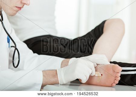 Doctor Peeling Bandage Off Patient Foot Injury