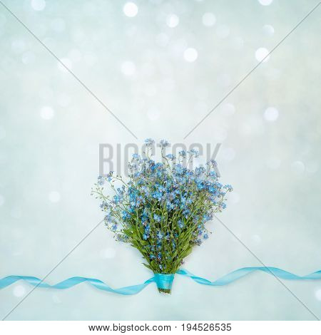 Beautiful spring bouquet of flowers forget-me-not and ribbons on a soft blue background. Springtime. Flat lay. Square Image Wallpaper With Copy Space