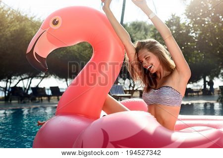 Young and sexy girl having fun and laughing on an inflatable giant pink flamingo pool float mattress in a bathing suit. Attractive tanned woman lies in the sun on vacation on Maldives