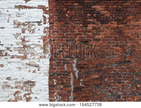 old red brick wall half painted in old peeling white paint or whitewash