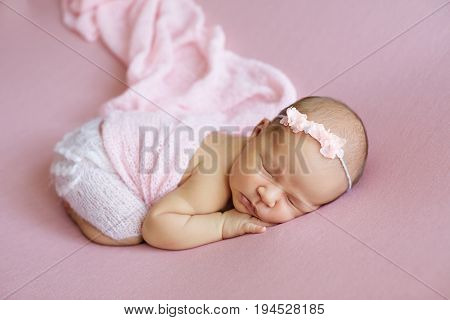 New born baby wearing a pink head band and tutu.