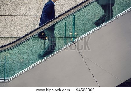 Japan, Tokyo, Tokyo International Forum, two men ascending escalator, mid section