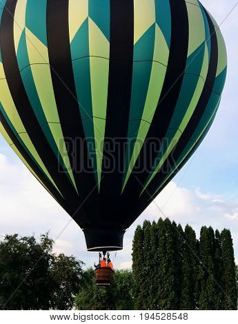 A black green and yellow Hot Air Balloon begins its ascent from Ochoco Creek Park in Prineville in Central Oregon on a summer morning.