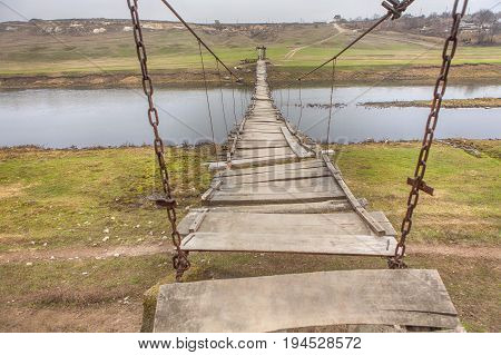 rural scene with hanging bridge over the river