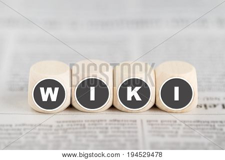 The word wiki on cubes on a newspaper
