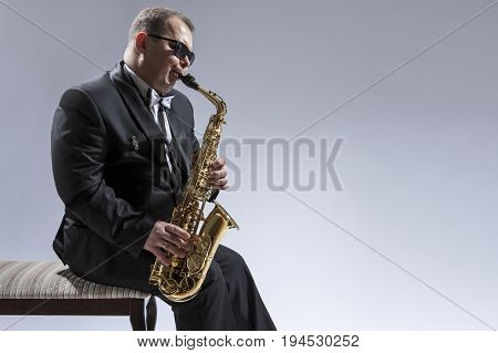 Music Concepts. Portrait of Mature Relaxed and Thoughful Caucasian Saxophone Player in Sunglasses Playing the Saxophone While Sitting on Chair in Studio Environment. Horizontal Image