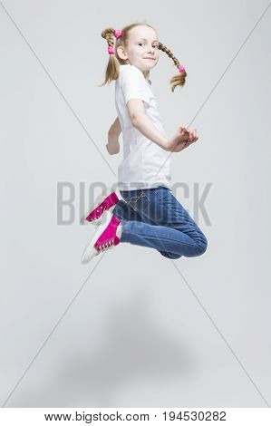 Portrait of Happy Smiling Caucasian Blond Girl With Pigtails Making a High Jump in Studio. Against White Background. Vertical Image Orientation