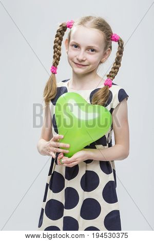 Portrait of Funny Caucasian Blond Girl With Pigtails Posing in Polka Dot Dress Against White. Holding Green Air Balloon. Vertical Shot