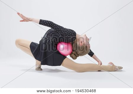 Sport Concepts. Caucasian Female Rhythmic Gymnast In Professional Competitive Black Sparkling Suit Doing Backbend Stretching Exercise With Ball in Studio On White. Horizontal Image Composition