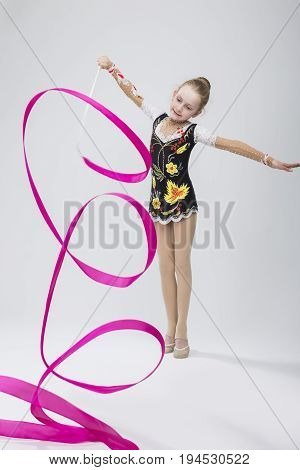 Portrait of Caucasian Female Rhythmic Gymnast In Professional Competitive Suit Doing Artistic Ribbon Spirals Exercises in Studio On White. Vertical Composition