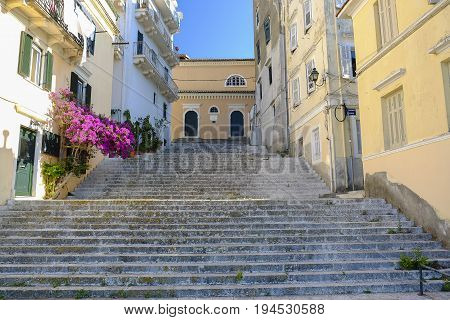 Typical street in old town of Kerkyra Corfu town with stairs and blooming bougainvillea on the island Corfu Greece.