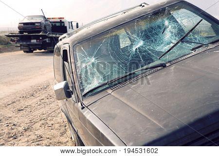 Car with broken windshield on roadside