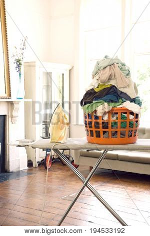 View of a laundry basket with iron on ironing board at home