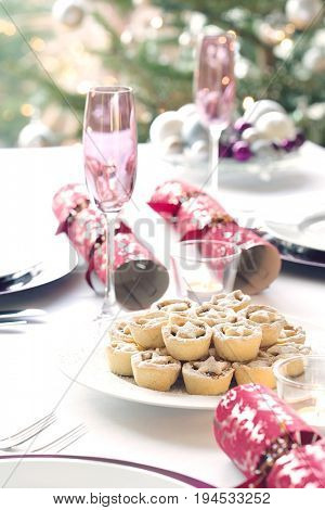 Christmas crackers; champagne flutes and mince pies on dining table