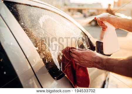 Male hand with tool for washing windows, car wash