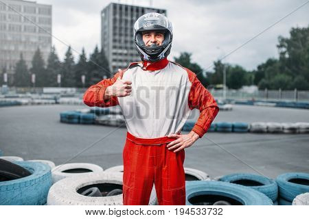 Kart driver in helmet, karting track on background