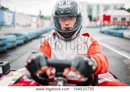 Carting race, go kart driver in helmet, front view