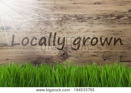 English Text Locally Grown. Spring Season Greeting Card. Sunny Aged Wooden Background With Gras.