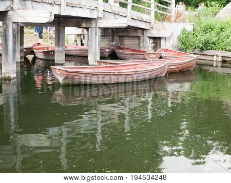 Several Wooden Row Boats Moored Under A Bridge