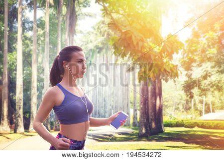 Slim female jogger with headphones in summer park