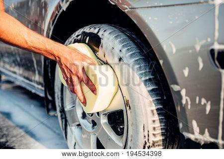 Male hand rubbing car wheel with foam, carwash