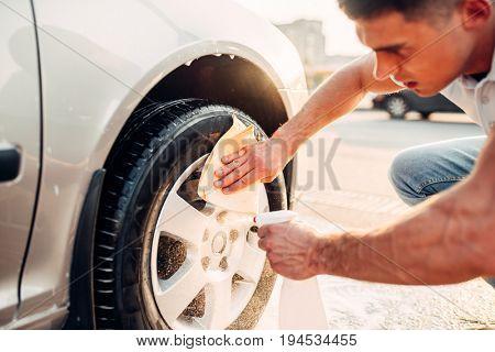 Man with car rims cleaner, carwash