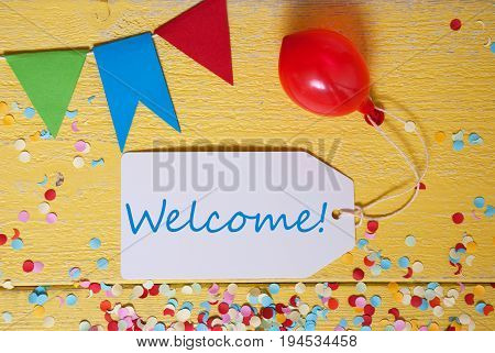 White Label With English Text Welcome. Party Decoration Like Streamer, Confetti And Balloon. Flat Lay Or Top View. Yellow Wooden Background