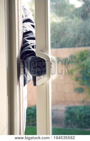 Burglar breaking into house, close-up of hand