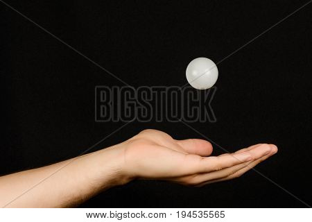 Men's Hand Which Catches The White Plastic Ball Isolated On Black Background