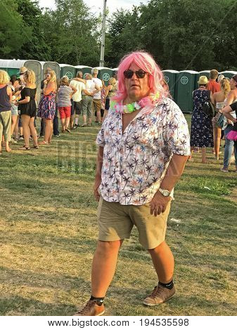 SOUTHAMPTON UK - July 8 2017: Lets Rock Southampton 80s music festival in Southampton UK. Man with a pink womans wig walking out of the toilet area.