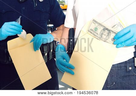 Midsection of two police officers inserting dollars and drug packet in envelope during investigation