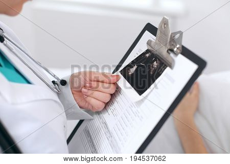 Close-up of a female doctor holding application form with ultrasonography while consulting patient.