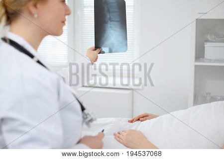 Female Doctor examines an X-ray picture of the spine next to patient lying in the bed in hospital.