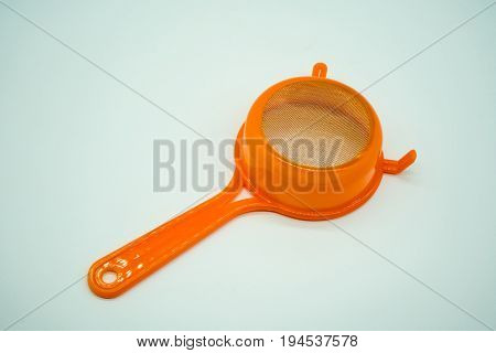 Mini kitchen sieve with orange plastic handle isolated on white background. Close up view of round metal straine