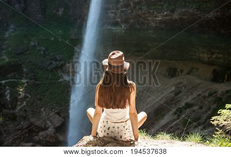 beutiful women in hat looking at the waterfall