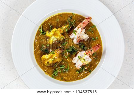 Prawn curry served with parsley on white plate