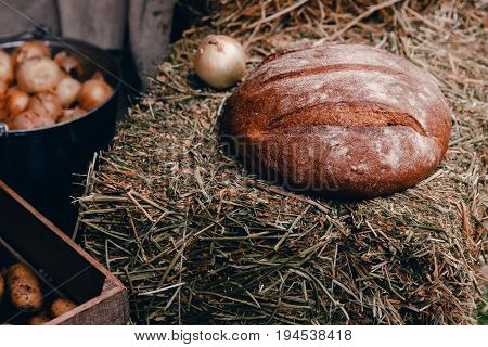 Peasant food in the farmer's style: baked bread, onions, potatoes on bales of hay. Concept Old Russian food, rustic style.