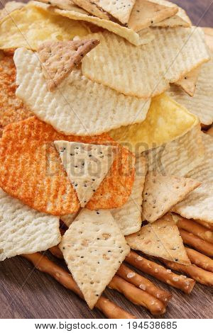 Salted Crisps, Breadsticks And Cookies On Rustic Board, Concept Of Unhealthy Food