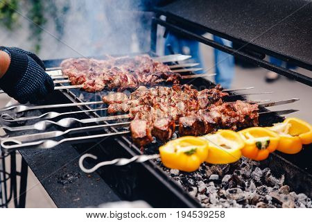 Cook grills a kebab grill and a shish kebab on charcoal, vegetables and meat in a marinade on a grill. Concept BBQ dinner.