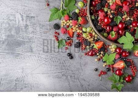Ripe berries from a garden with leaves on a stone plate. Mix of strawberries, currants, blackberries, cherries. Top view