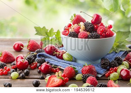 Assorted ripe berries from a garden in a bowl on a wooden board. Background of green leaves. Mix of strawberries, currants, blackberries, cherries.
