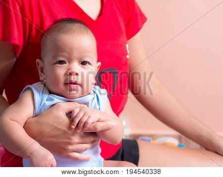 Close Up, Asian Infant In Mother's Arms.