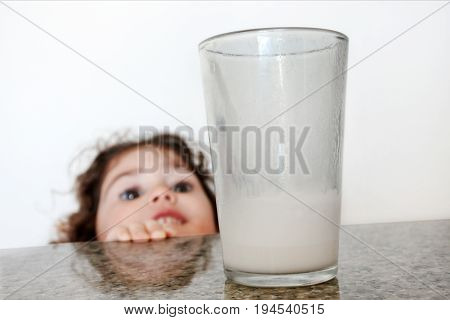 Cheeky little girl (age 3) wants to drink milk. Healthy Eating concept. Real people. Copy space