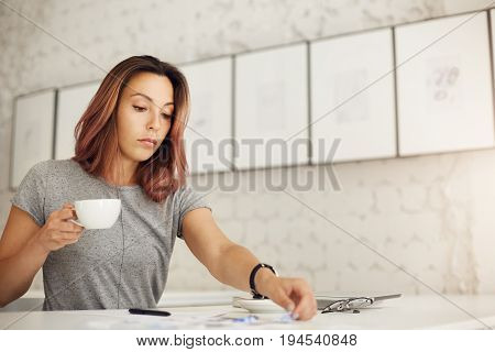 Creative worker doing her daily job drinking coffee resting from her overwhelming online life.